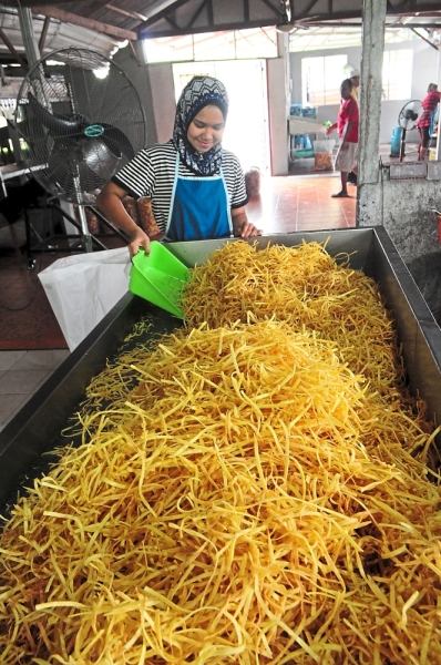 Nurul Imam Misdar sorting out fresh sweet potato crisps just out of the fryer at her parents' shop in Kampung Hulu Chuchoh. Prices here are cheaper than in the city.