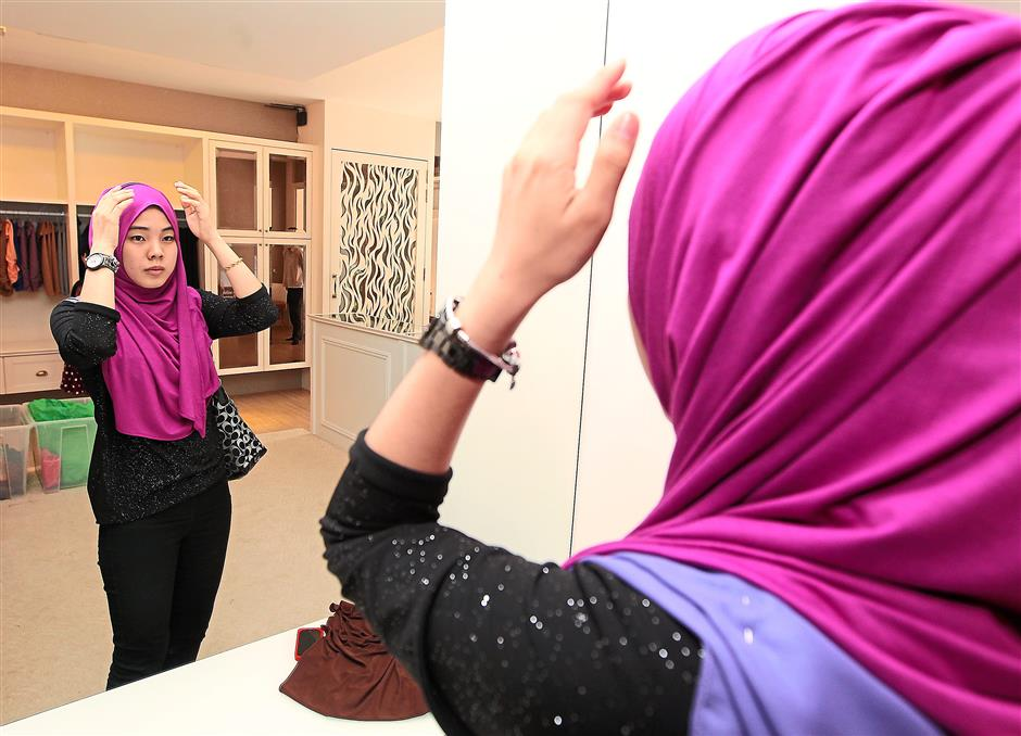 A customer trying out a Naelofar hijab at the boutique in TTDI, Kuala Lumpur.