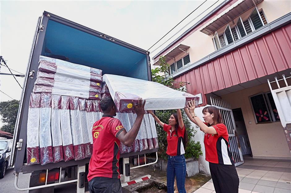Ting (second from right) and Goodnite senior marketing executive Bobo Wong (right) helping out when the 30 donated single foam mattresses arrived at the Pusat Jagaan Orang Tua Gam Yan in Ampang.