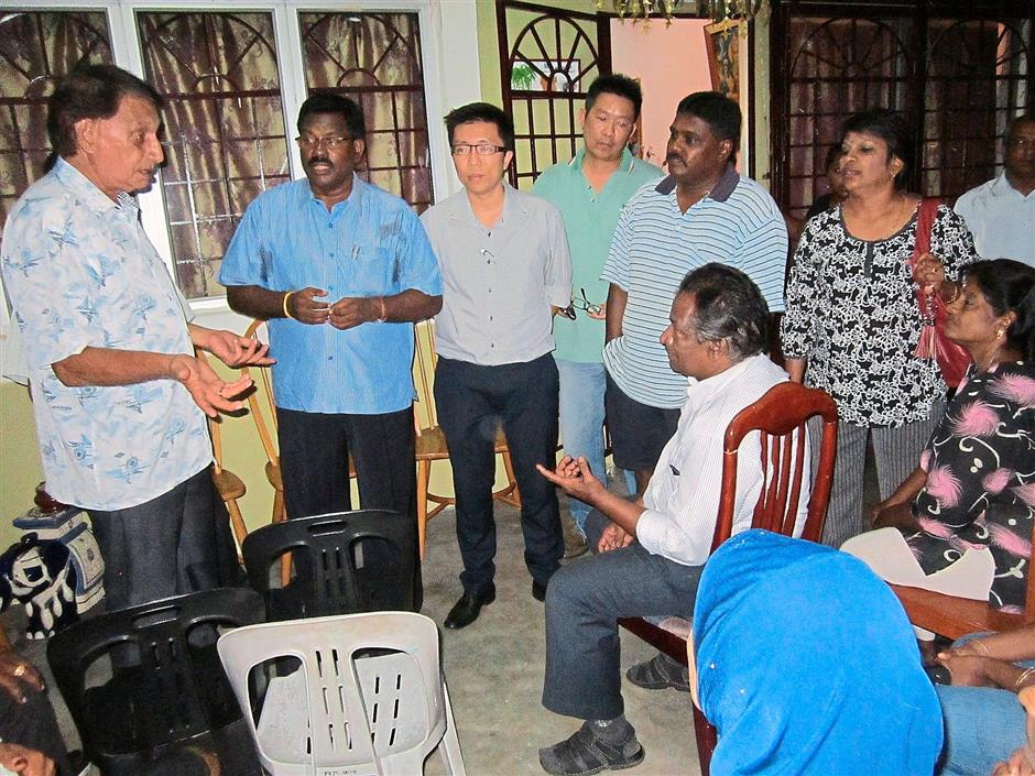 Discussion: Nik (standing far left) meeting with the affected residents while Raja (standing second left), Selayang MCA secretary Ryan Ng (standing third left), Wan (standing fourth left) listen on.