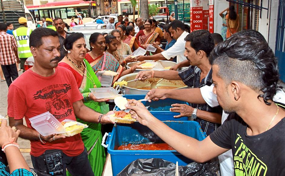 Enough to go round: Devotees being served vegetarian food in conjunction with the celebration near Sri Maha Mariamman Temple in Queen Street.