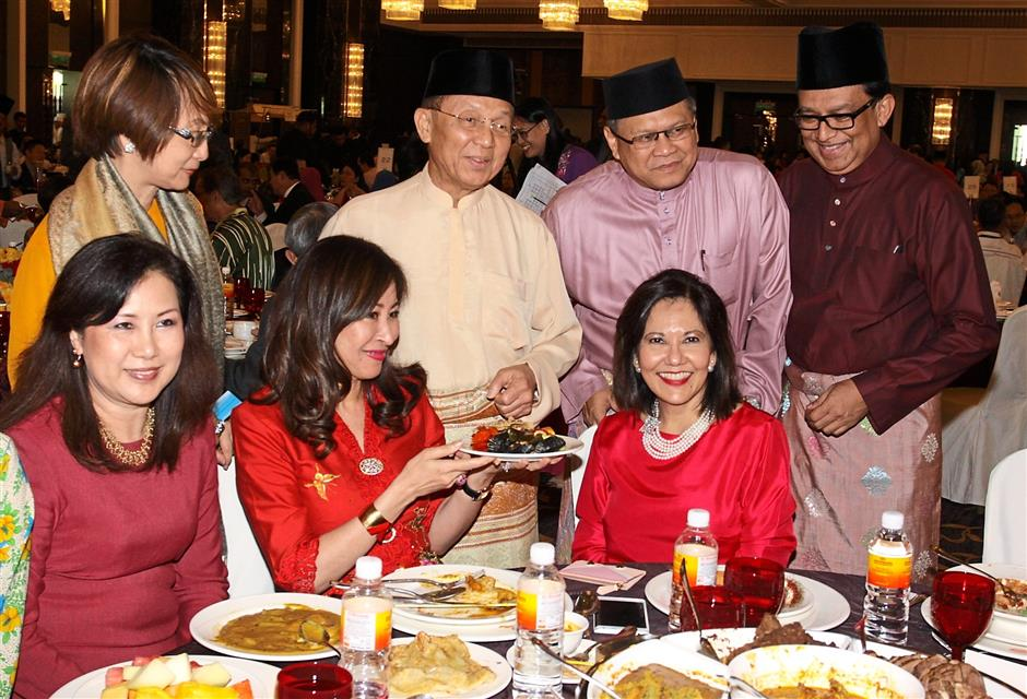 Good food and company: Azman (standing, second from left) enjoying himself at the Hari Raya open house organised by the AmBank Group in Kuala Lumpur.
