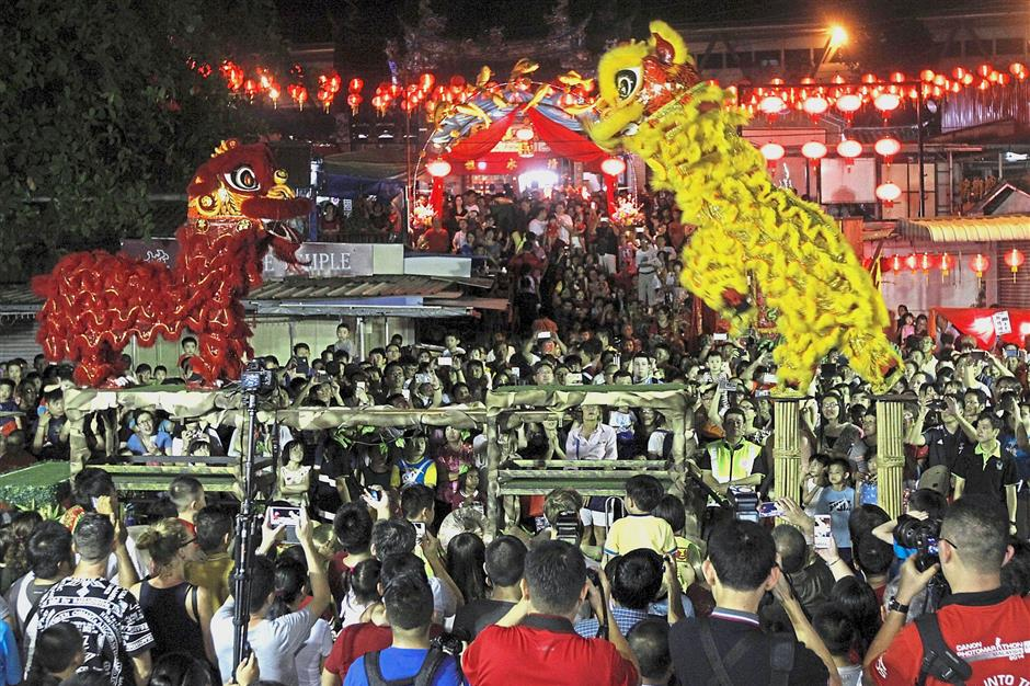 A crowd gathering to watch the exciting lion dance on stilts performance during the flame-watching ceremony.