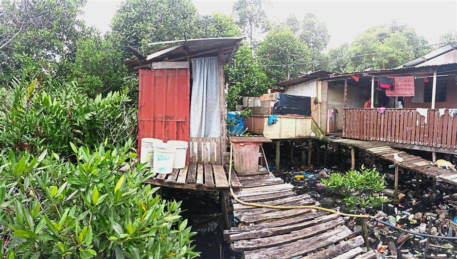 Better infrastructure needed: An outhouse in a coastal village in Sandakan that is built over a river near the house.