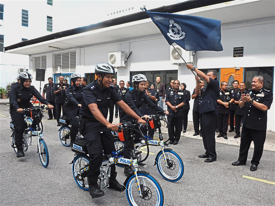Comm Chuah flagging off a police e-bike team. With him is his deputy Comm Datuk Roslee Chik (right).