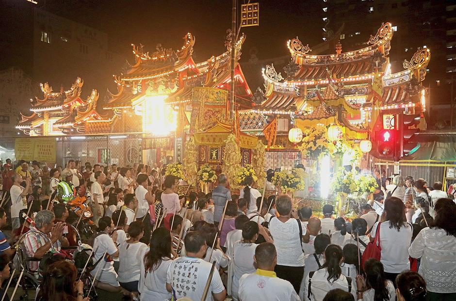 A huge crowd of devotees gathering with lit joss sticks to offer prayers before sending off the float parked outside the Kuan Im See Temple in Burmah Road on the last day of the Nine Emperor Gods Festival in George Town, Penang. — Photos: ZHAFARAN NASIB/The Star
