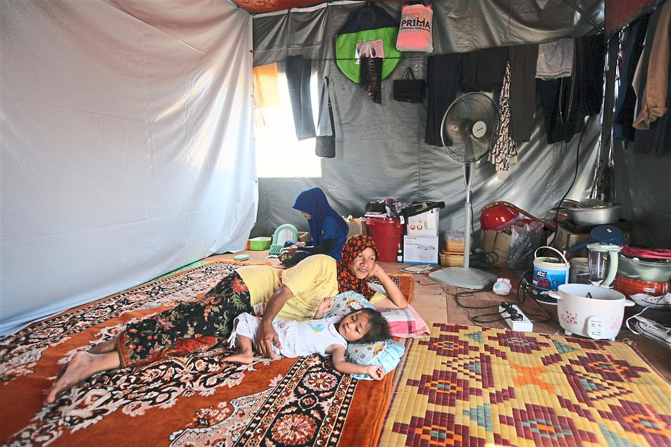 Mariam Majid and her daughters cant bear to stay in the tent in the afternoon heat.