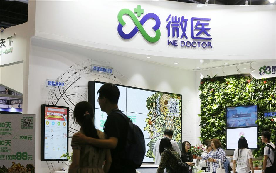 People walk past the booth of online healthcare solutions platform WeDoctor at the Global Mobile Internet Conference (GMIC) in Beijing, China April 29, 2017. Picture taken April 29, 2017. REUTERS/Stringer  ATTENTION EDITORS - THIS IMAGE WAS PROVIDED BY A THIRD PARTY. CHINA OUT.
