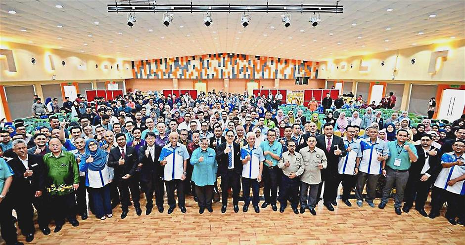 Dr Ramzah (middle, in black suit) posing for a photograph with participants of the forum.