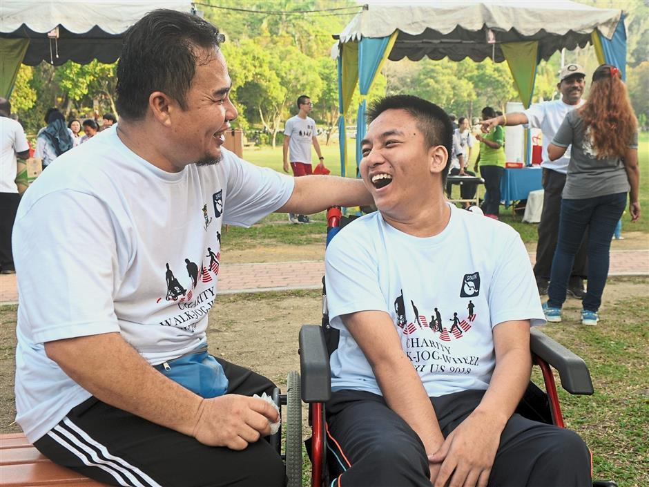 Abdul Razak (left) spending time with Muhd Aiman after the event at the Penang City Park.
