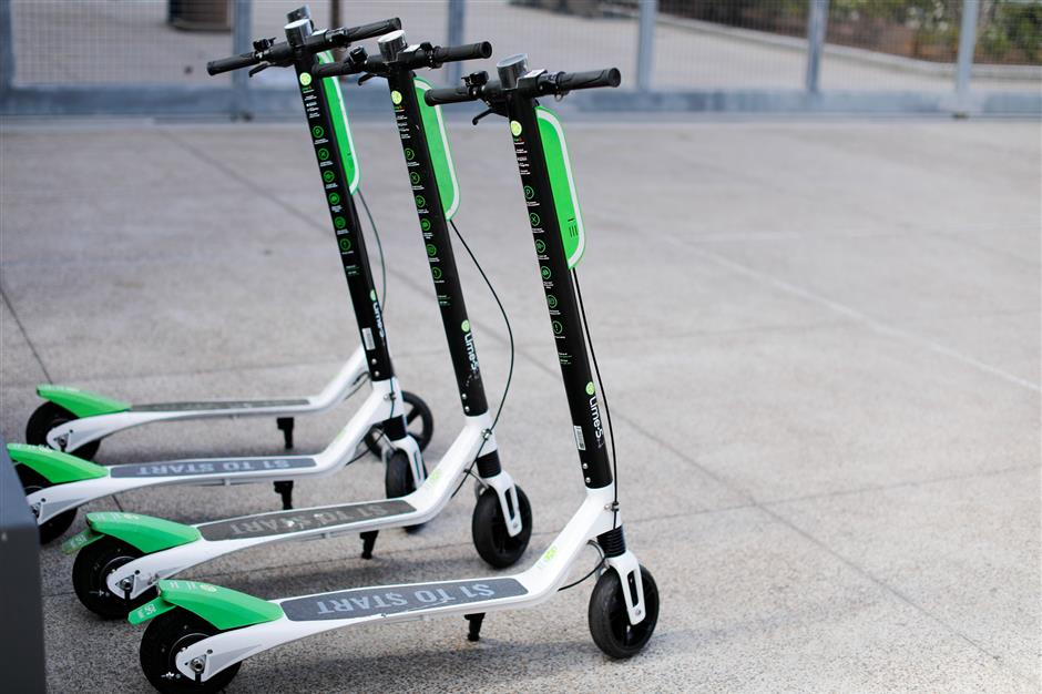 Smart phone app time-of-use electric scooters from Lime-S are shown parked along a sidewalk in San Diego, California, U.S., May 17, 2018.    REUTERS/Mike Blake