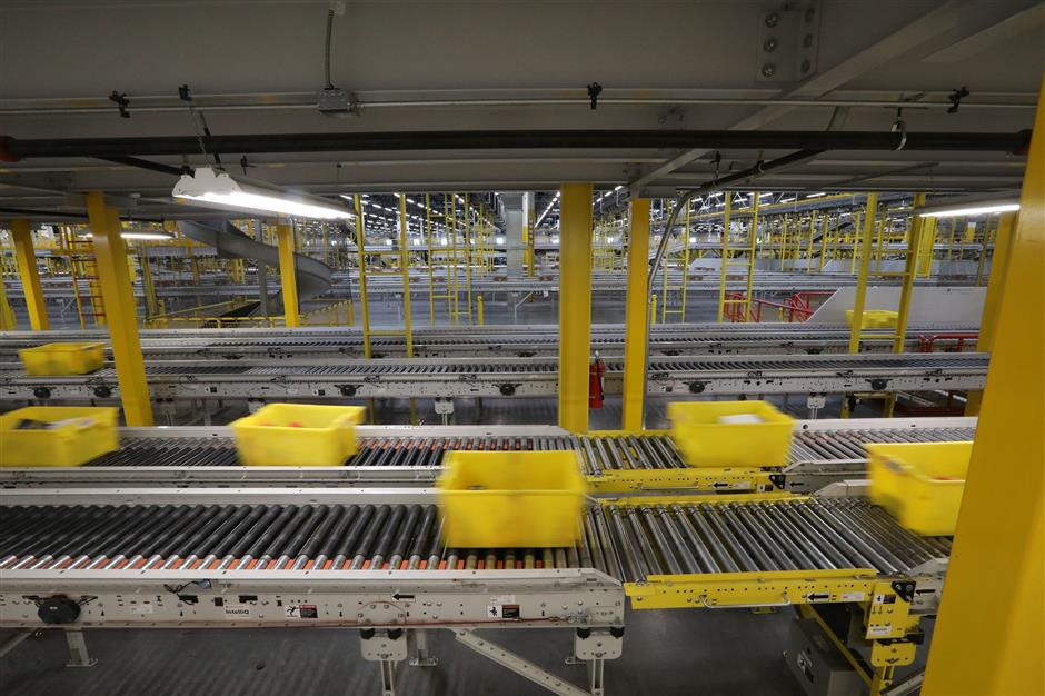 Totes with packages in them are moved quickly to their next destination in the Kent warehouse, called a fulfillment center. (Alan Berner/Seattle Times/TNS)