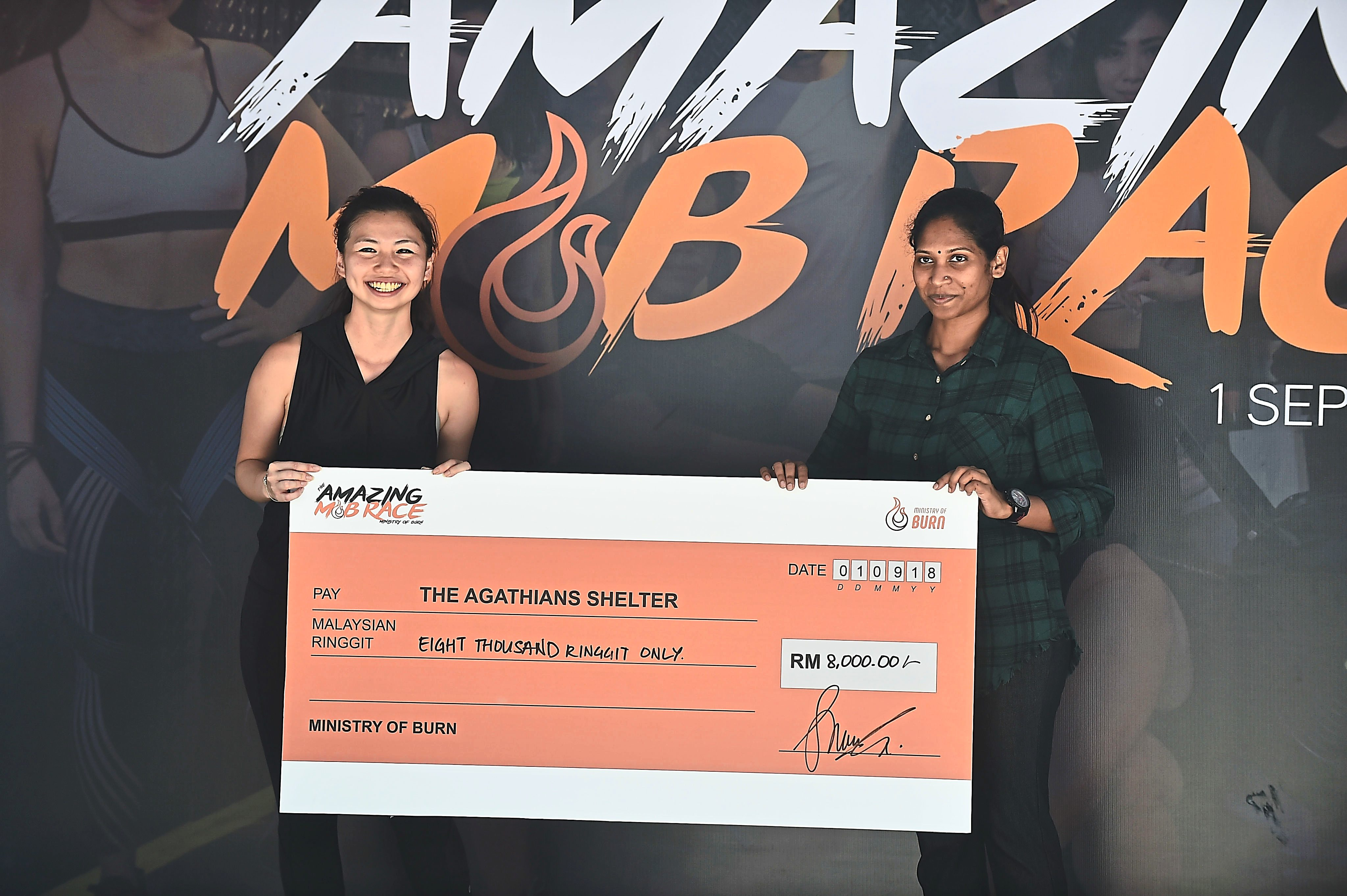 Ng (left) handing over a mock cheque to Agathians Shelter executive council member M. Inthira.