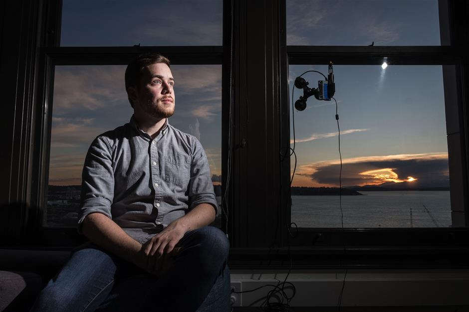 From Alan Hussey's 19th-floor office window inside Smith Tower, he gets an unobstructed view of the sunset over Elliott Bay and the Olympic Mountains. He captures it on a web camera -- mounted here on the window -- and posts it every day on Twitter at @GoldenHourSEA. (Dean Rutz/Seattle Times/TNS)