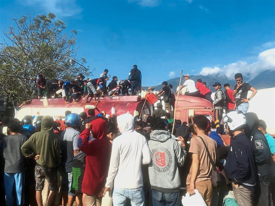 Desperate for aid: People queuing to get gasoline from a truck in Palu. — AP