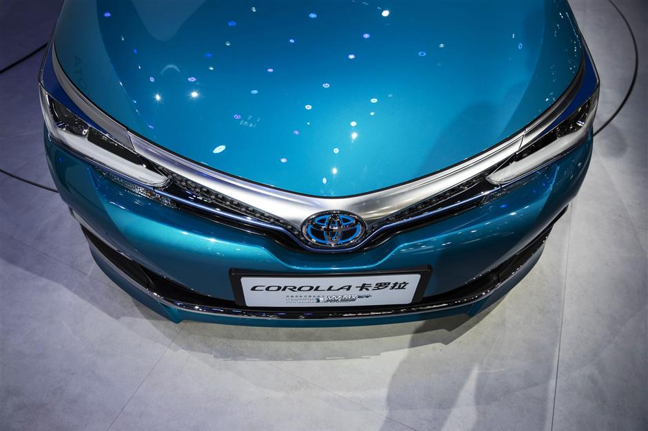 The Toyota Motor Corp. plug-in hybrid Corolla vehicle stands on display at the Beijing International Automotive Exhibition in Beijing, China, on Wednesday, April 25, 2018. The Exhibition is a barometer of the state of the worldu2019s biggest passenger-vehicle market. Photographer: Qilai Shen/Bloomberg