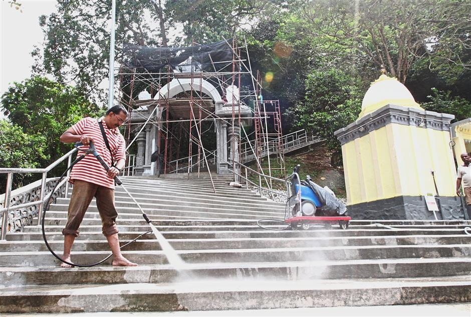 A volunteer using a high pressure hose to clean the steps of the Arulmigu Balathandayuthapani Hilltop Temple.