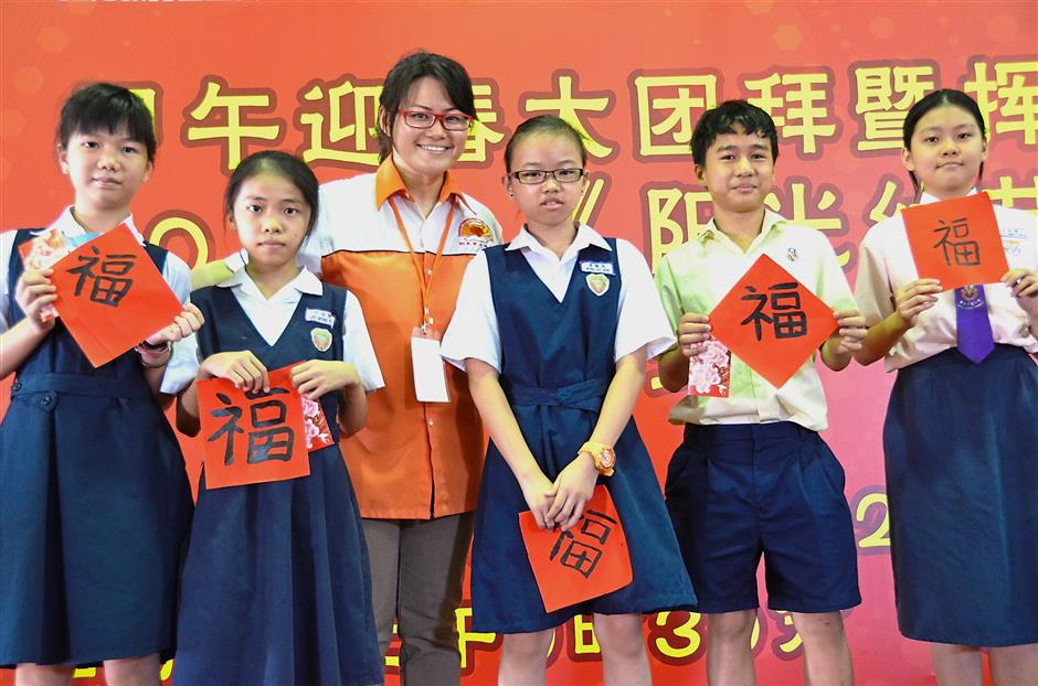 Chan, who is executive secretary of the Sunlight Education Fund, is seen here with SJK(C) Salak South students after presenting a cheque to the school during a Chinese New Year event in 2014.
