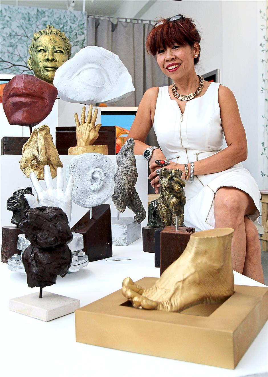 Fond of sculpting: Xie showing her sculptures that are on sale at the exhibition.