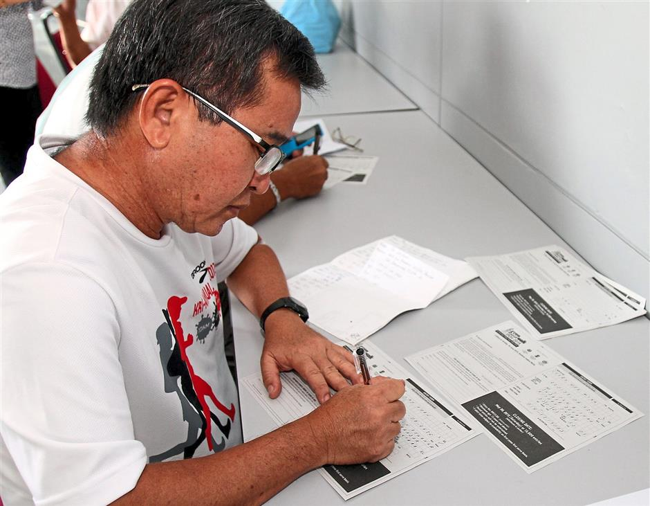 Going for the dozen: Cheah filling up twelve registration forms on behalf of his colleagues.