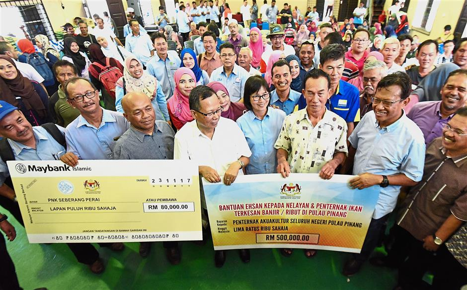 Ahmad Shabery (front, second right) posing with fish farmers after presenting the contributions to them in Pulau Aman in Penang.