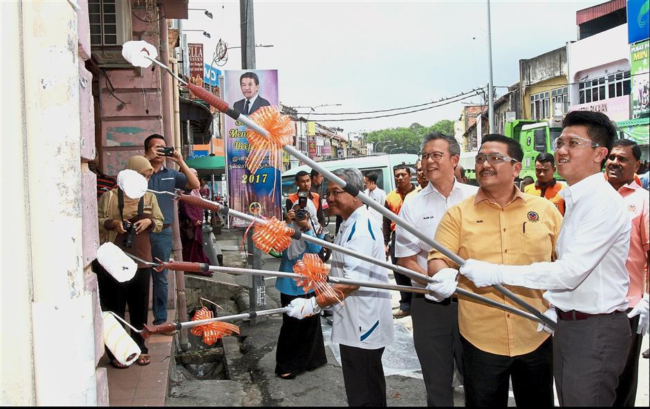 Deputy Education Minister Datuk Chong Sin Woon (right) painting the facade of an almost century-old shop located in old Nilai in a campaign to 'beautify' the town recently. – filepic