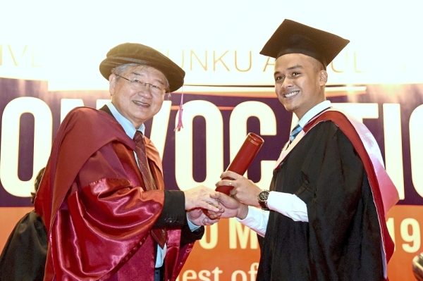 (Above) Prof Tan (left) presenting a scroll to Bachelor of Communication (Hons) Public Relations graduate S. Kugganesh.(Left) Some of the graduates at UTAR's 28th convocation in Kampar.