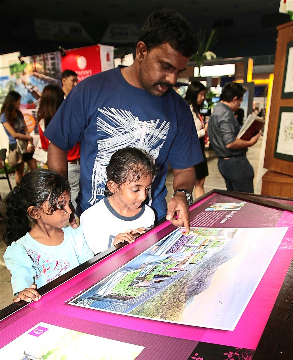Options aplenty: Kanan and his daughters checking out a housing project at the Penang International Property Expo 2015 which is part of the Penang Property Summit.
