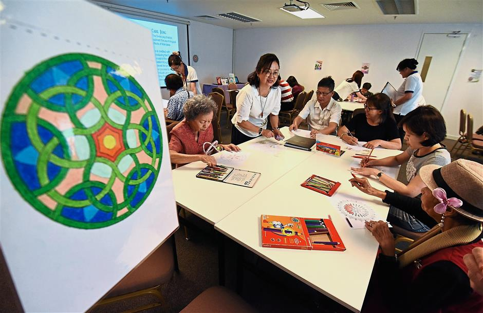 Chin (standing, second left) guiding participants at the mandala colouring workshop. — Photos: MUSTAFA AHMAD/The Star