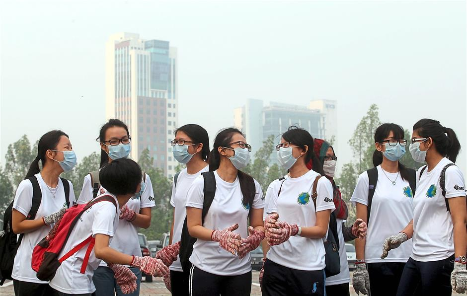 Not taking chances: Students wearing masks while outdoors in Shah Alam where the air quality dipped to unhealthy levels. —? AZHAR MAHFOF/The Star