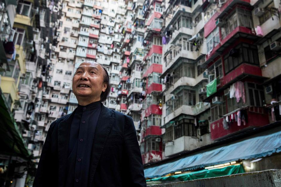 This picture taken on January 20, 2019 shows resident Tony Hui posing at a popular Instagram spot in Hong Kong. - For smartphone-wielding hordes of tourists, Hong Kong boasts a host of must-have Instagram locations -- but crowds of snap-happy travellers are testing local patience and transforming once quaint pockets of the bustling metropolis. (Photo by Isaac LAWRENCE / AFP) / TO GO WITH HongKong-lifestyle-tourism-photography, FEATURE by Elaine YU