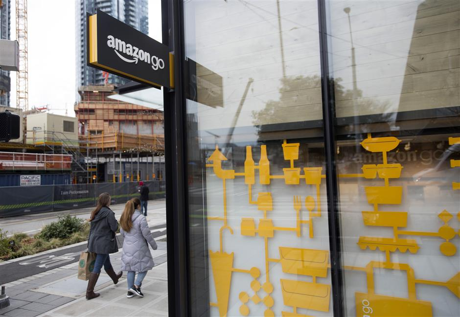 Pedestrians walk past the Amazon Go store in Seattle, Washington, U.S., on Wednesday, Jan. 17, 2018. After more than a year of testing with an employee-only focus group, Amazon Go opens to the public Monday in downtown Seattle, putting to the test the online retailer\'s technology that lets shoppers grab what they want and leave without paying a cashier. Photographer: Mike Kane/Bloomberg