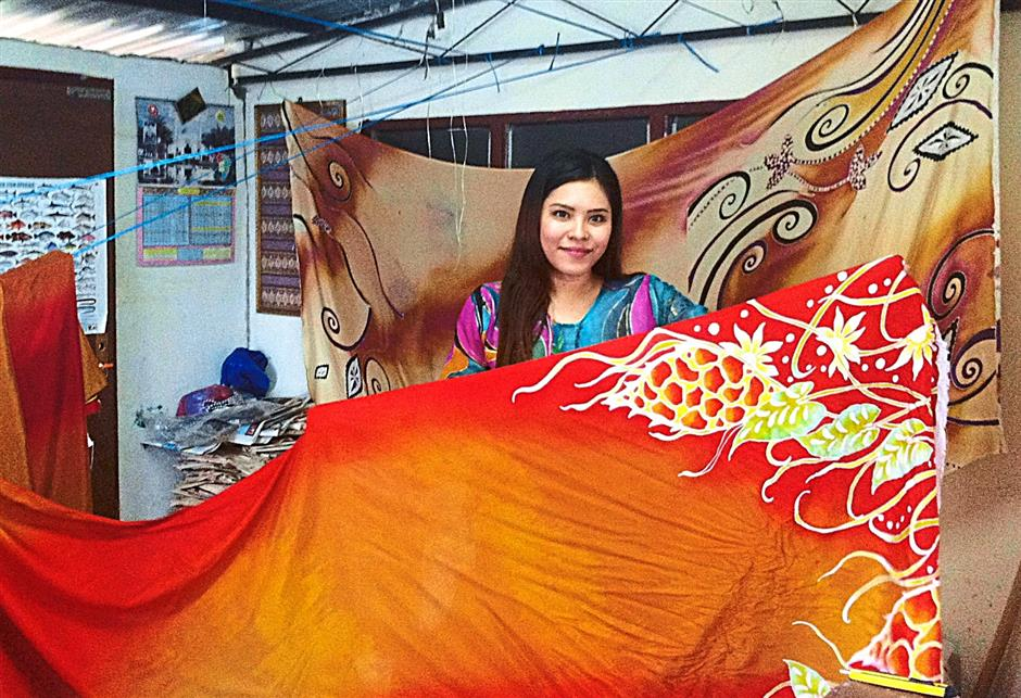 Husna showing off batik produced by her factory in Baling, Kedah.