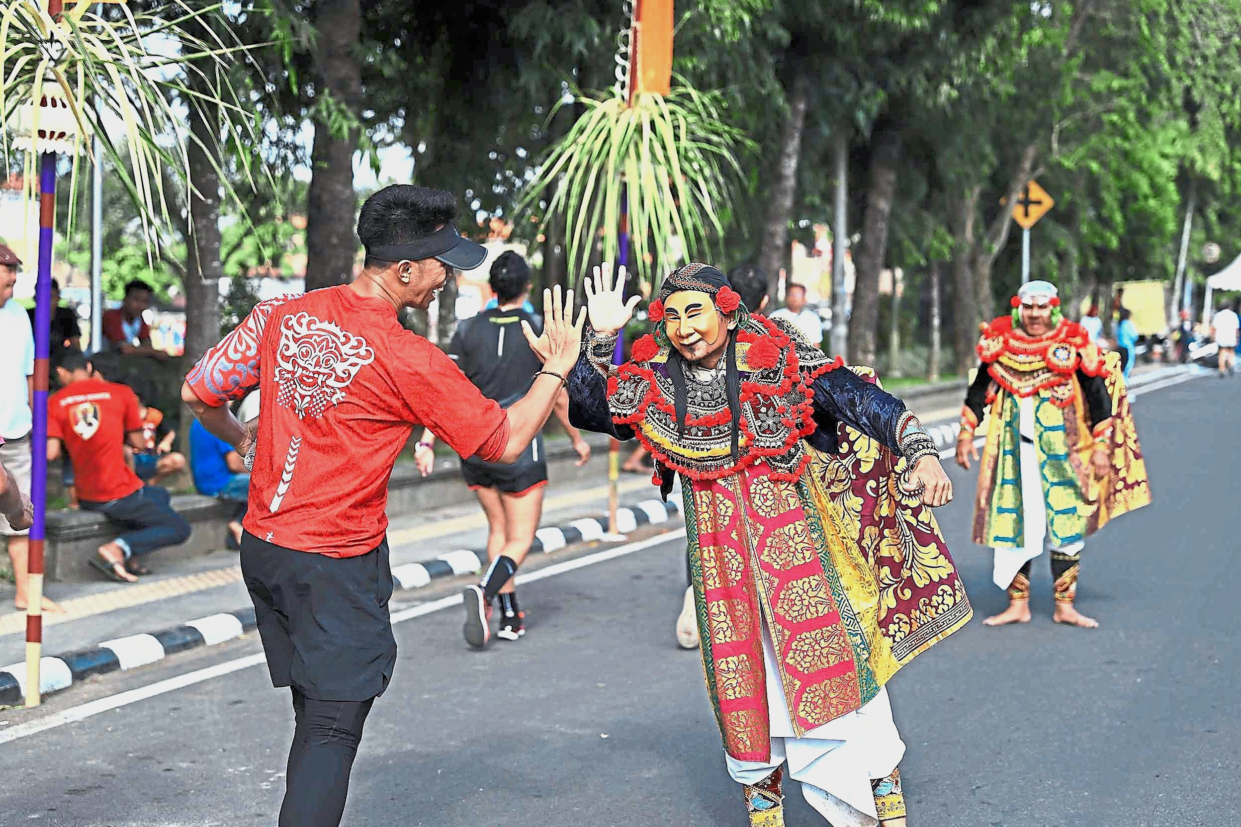 A traditional Balinese dancer cheering and giving a high-five to a passing runner.