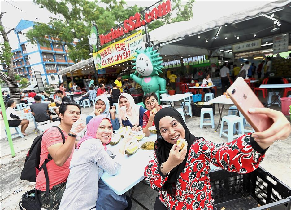 Shafinaz Izyani Abd Jabar (right), 36, taking a wefie with her colleagues while savouring the cheaper durian options available in the market.