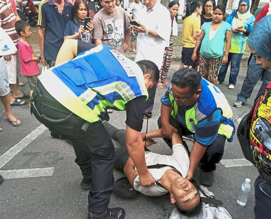 Miri police arresting a snatch-thief who was apprehended by members of the public in the Boulevard Commercial Centre on Friday afternoon.for News nibbles