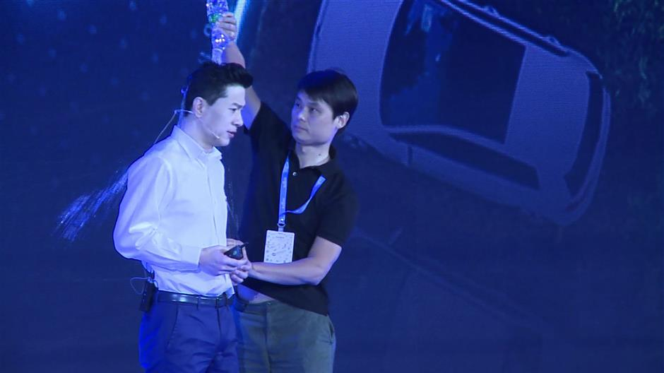 This framegrab taken from AFPTV shows a man (R) pouring water Baidu co-founder and CEO Robin Li during Baidu Create 2019 in Beijing on July 3, 2019. - A man burst on to a stage and poured water over the head of Li as the founder of China\'s dominant search engine spoke at a company-sponsored event on Artificial Intelligence. (Photo by QIAN Ye / AFPTV / AFP)