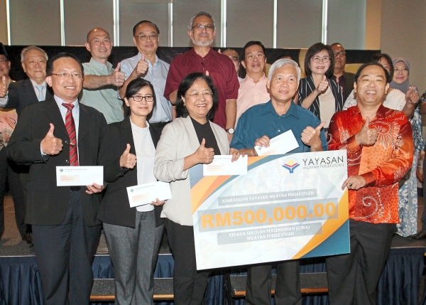 Posing with the cheques they received from Khalid (back row, in red shirt) are (front row, from left) Confucian Private Secondary School principal Ng Beng Pen, Kuen Cheng High School principal  Dr Chua Lee Lee, Chong Hwa Independent High School principal Cheong Moey Lian and Tsun Jin High School principal Cheng Ah Swee. On the right is Chong Hwa board of directors chairman Tan Sri Lim Keng Cheng.