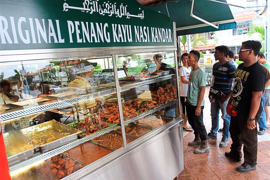By lunch time, a crowd gathered at Original Penang Kayu Nasi Kandar, forming a long line of customers waiting to pick from the various types of dishes prepared for the day. Prize presentation for Star Food Awards best Nasi Kandar to Kayu Nasi Kandar. ......Sam Tham/Star