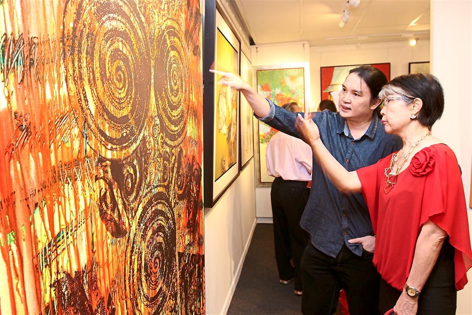 Telling his story: Chap (left) talking about his mixed-media painting titled Borneo Bloody Roots (Bernafas) to Datin Ho Choy Meng, one of the visitors at the newly opened Jeth Art Gallery,