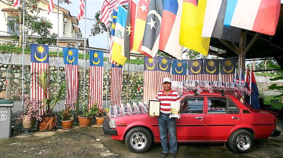 Patriotic: Khamis poses in front of his car which is decorated with dozens of flags at his home.