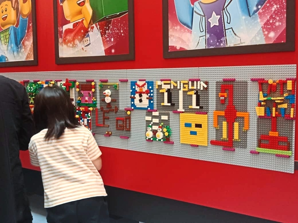 Various Lego mosaic pieces created by the children on display on the Lego Christmas mosaic wall.