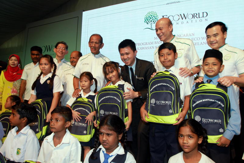Deputy Education Minister Datuk Chong Sin Woon (third from right) handing over a school bag to a pupil at Eco World foundation extends students aid programme in Puncak Alam ,Kuala Selangor with (right) Eco World Development group executive director Datuk Voon Tin Yow , (second from right) Eco World Foundation chairman Tan Sri Lee Lam Thye and (fourth from right) Eco World Foundation trustee Tan Sri Mohd Radzi Sheikh