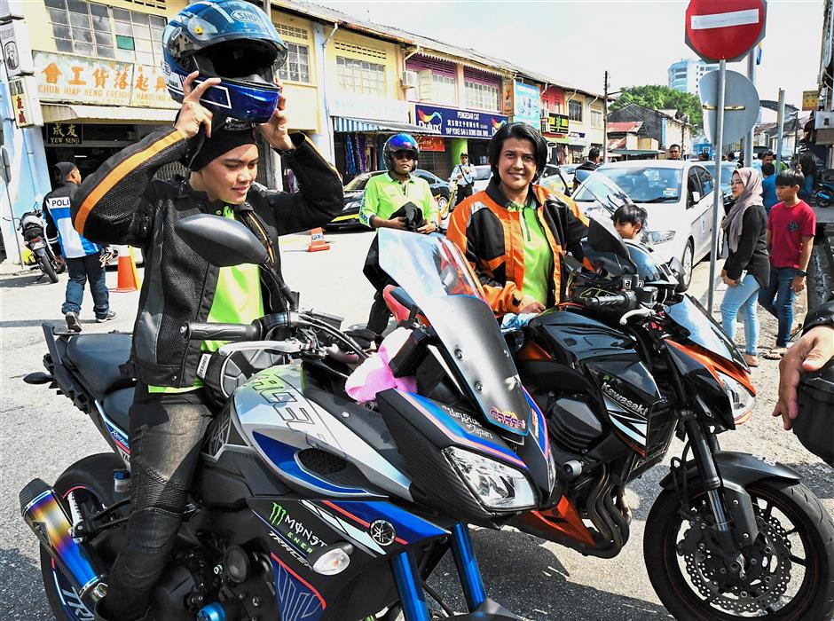 ASP Nur Hidayah (putting on helmet) and ASP Norhastinarahayu (centre) say they are proud to be part of the convoy and help raise funds for retired police officers.