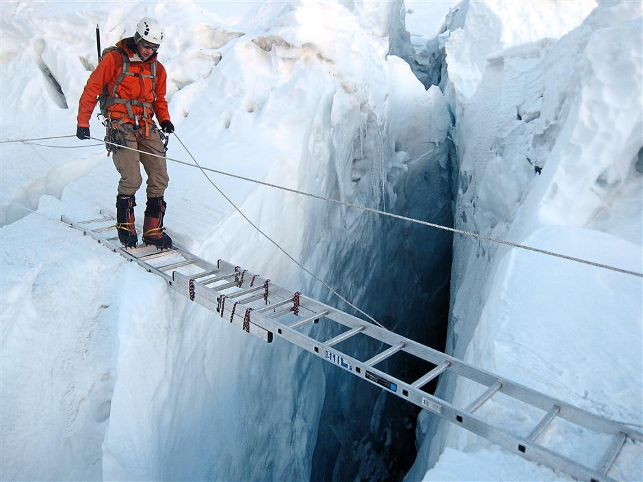 A climber using a ladder to cross a crevasse on the Khumbu Icefall on Mount Everest.