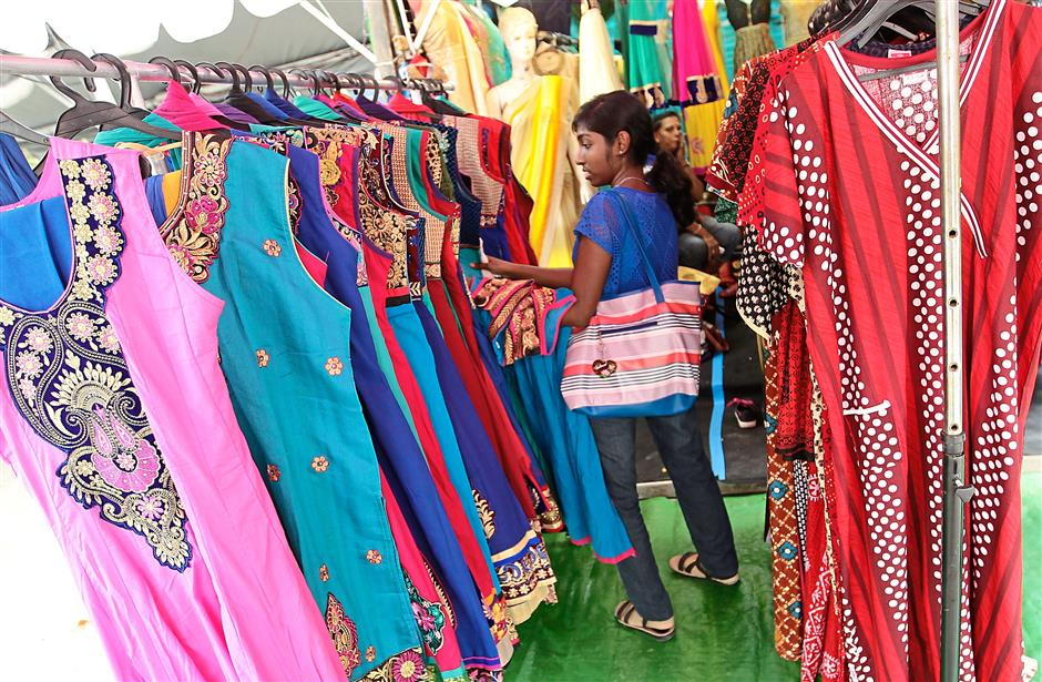 A shopper looks through rows of colourful punjabi suits for sale at the Deepavali bazaar in Jalan Masjid India. AZMAN GHANI / The Star