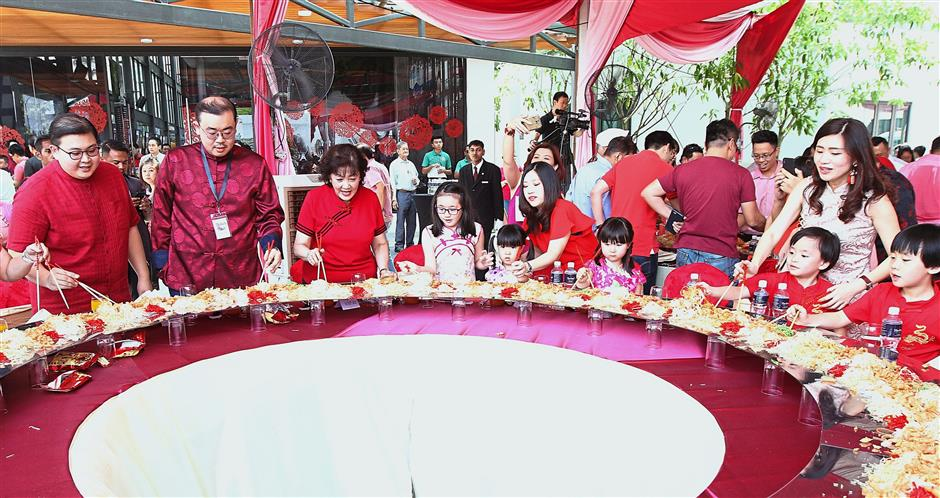 (From left) Aik Chong, Aik Kiong and Sua tossing yee sang with guests at the AikBee Group Grand Chinese New Year Open House.