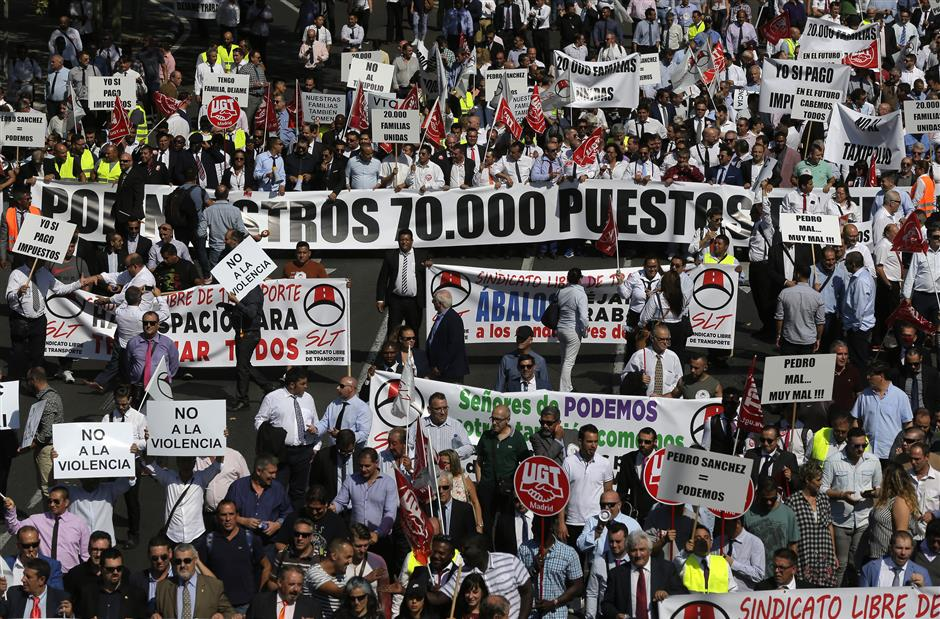 Drivers working for companies like Uber and Cabify march during a protest in Madrid, Spain, Thursday, Sept. 27, 2018. Hundreds of black vehicles of app-based ride-hailing services are blocking a central artery in the Spanish capital to protest the government\'s plan to approve new rules that would limit their operations. (AP Photo/Manu Fernandez)