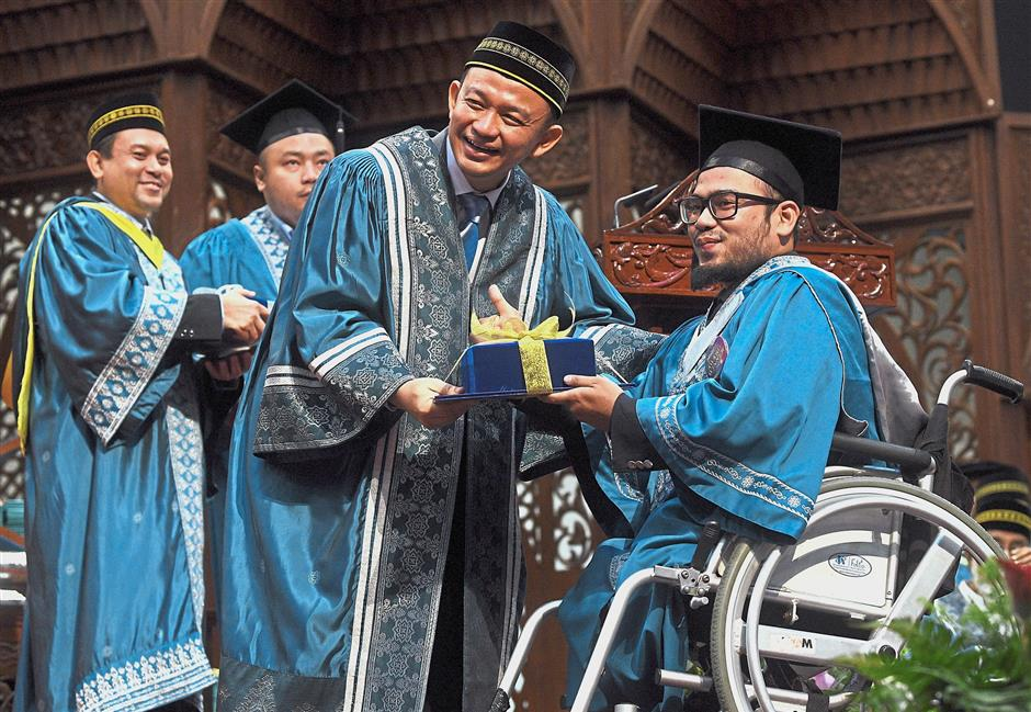 Dr Maszlee (left) presents a co-curriculum achievement award to Azzrulkhan Hasrullah Matsah, a special needs climber who reached the Everest Base Camp last May during the recent IIUM convocation at the Gombak campus. — Bernama