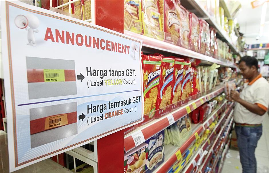Getting ready: A worker punching price tags on the goods at a store in  Petaling Jaya